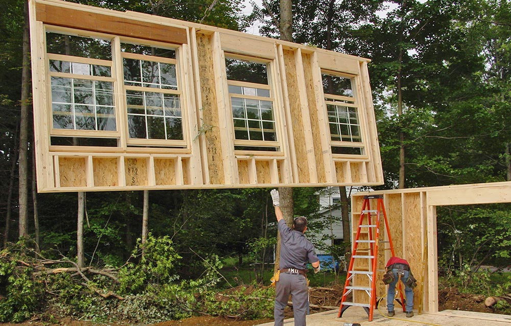 Builders guide panelized wall into place on home site
