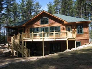 Custom home with wood siding and large deck