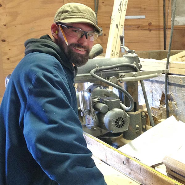 Builder with beard wearing safety goggles and pencil behind ear